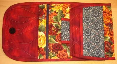 En ficka med dragkedja och utrymme där bakom, en pennhållare och en lös fläpp med fickor på båda sidor.